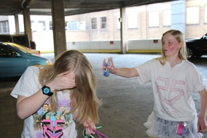 The girls spraying their hair with glitter.