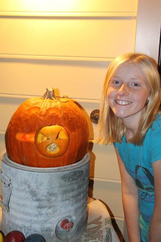 Molly carved a big pumpkin eating a small pumpkin.
