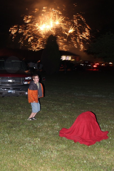 "Ozzie danced to the ""Booms"" while Tyler snuggled under the blanket to keep warm. (Tyler is the red lump on the ground.)  :)"
