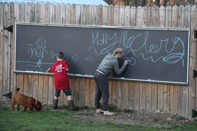 The kids coloring o the outdoor chalkboard.
