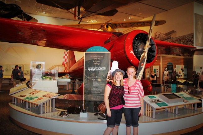 The girls posing next to plane of one of their historical heroes... Amelia Earhart!